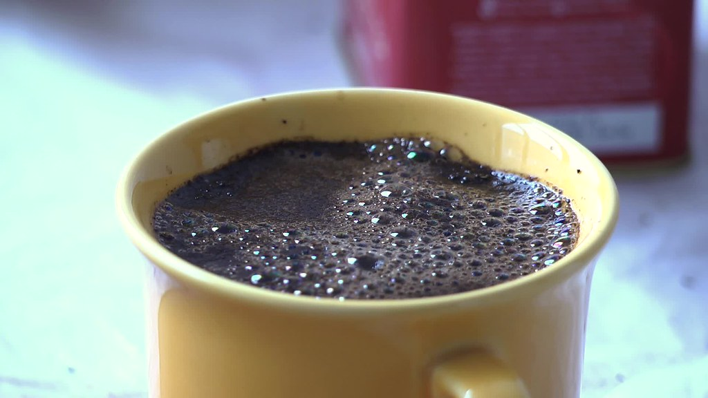 Stirring brewed coffee in a yellow ceramic cup with a silver spoon. Slow motion free HD video