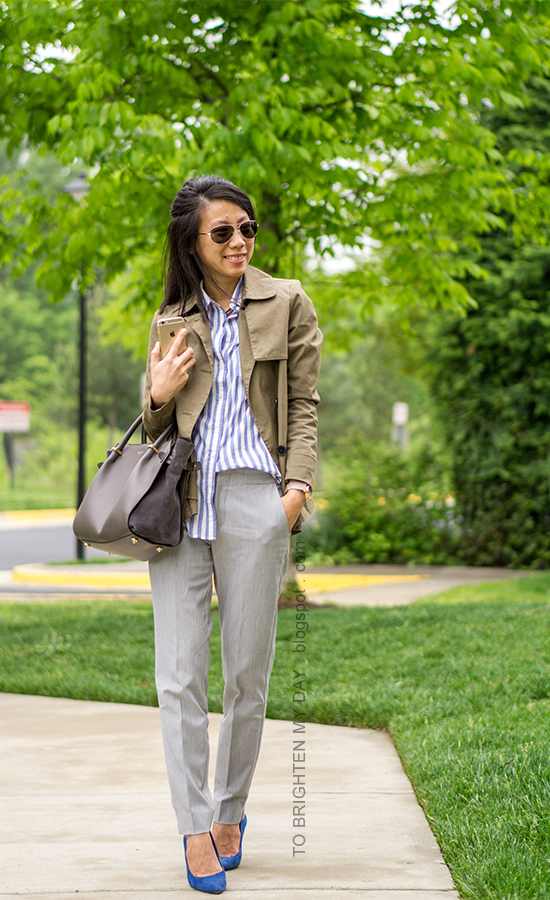 olive green swing trench, blue striped button up shirt, gray trousers, oversized watch, blue suede pumps