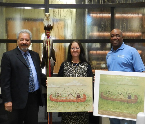 Larry Romanelli, with the Little River Band of Ottawa Indians Ogema (left) and NRCS Michigan State Conservationist Garry Lee (right) pose with artist Shirley M. Brauker, the winner of the agency's Native American Heritage Month poster contest. NRCS photo.