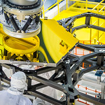 The robotic arm lifts and lowers a golden James Webb Space Telescope flight spare primary mirror segment onto a test piece of backplane at NASA's Goddard Space Flight Center in Greenbelt, Md. While the team practices the positioning that will be done on the actual telescope in the cleanroom, Dave Sime, an assembly crew chief, inspects the mirror placement from the underside of the backplane.
