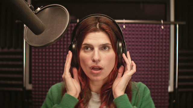 Lake Bell's Carol in a voice booth, wearing headphones