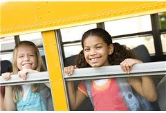 Girls at school bus windows