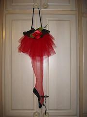 dance dress(0.0), ballet tutu(0.0), costume(0.0), pink(0.0), dress(0.0), lighting(0.0), dance skirt(1.0), flower(1.0), clothing(1.0), red(1.0), skirt(1.0),
