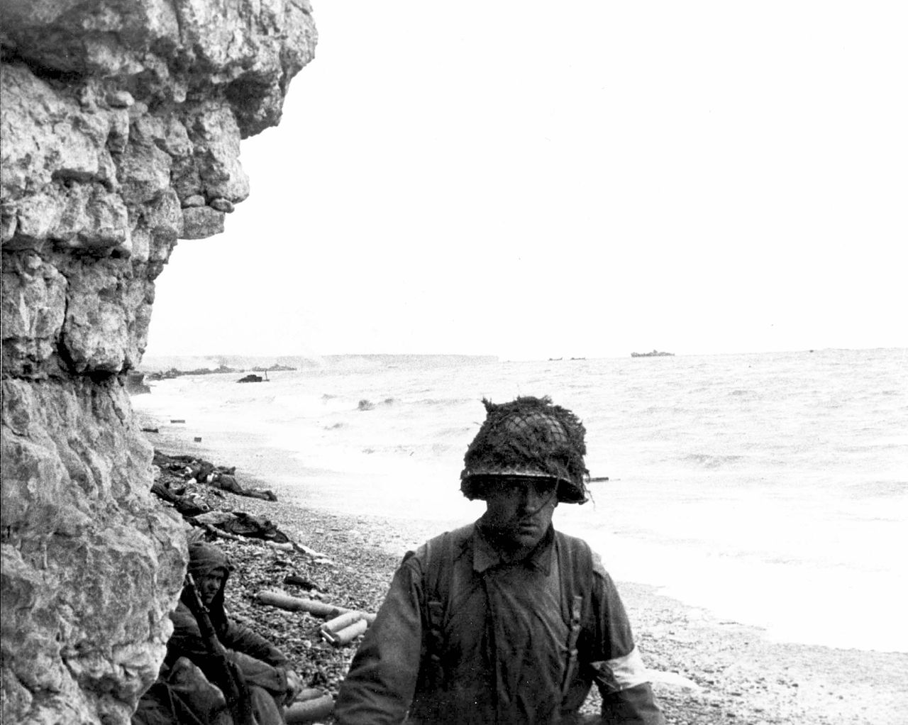 A medic of the 3d Bn., 16th Inf. Regt., 1st U.S. Inf. Div., moves along a narrow strip of Omaha Beach administering first aid to men wounded in the landing.