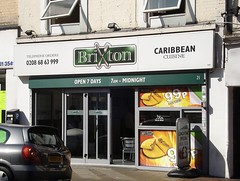 "A terraced shopfront viewed on a sunny day. A sign above the shop reads ""Brixton Caribbean Cuisine"". Two sliding doors on the front have been opened to let the air in."