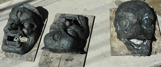 Grey Tibetan wrathful mask forms drying in the sun, three eyed sculptures on boards, near Tharlam Monastery, Tibetan Buddhist, Boudha, Kathmandu, Nepal