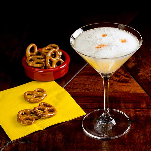 Pisco Sour Cocktail in cocktail glass, with pretzels