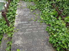 "A flat-topped grave overgrown with ivy.  The names ""Elizabeth Gresham"" and ""Samuel Lee Rymer"" are just visible, along with death dates and ages of 3 July 188-something (57 years) and 7 March 1909 (76 years) respectively."