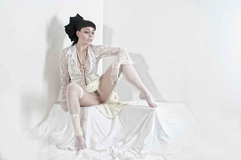 Open leg image of a dark haired girl wearing white lace