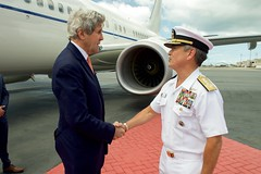 U.S. Navy Admiral Harry Harris, Commander of Pacific Command, greets U.S. Secretary of State John Kerry as he arrives at Joint Base Pearl Harbor-Hickam, Hawaii, on May 25, 2016, for a re-fueling stop and military briefing en route to Washington, D.C., from joining President Obama's trip to Vietnam. [State Department photo/ Public Domain]