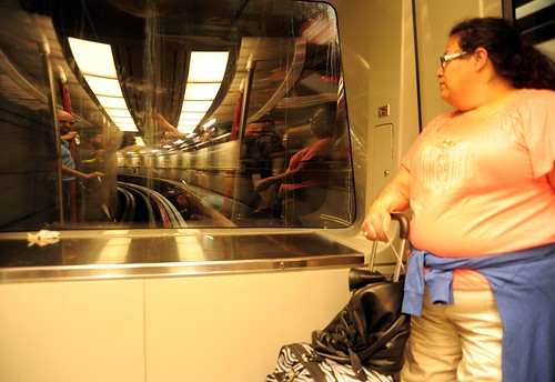Travel on the underground tram, a woman with her bags, looks into the reflection, Seatac Airport, N gates, Seattle / Tacoma, Washington, USA by Wonderlane