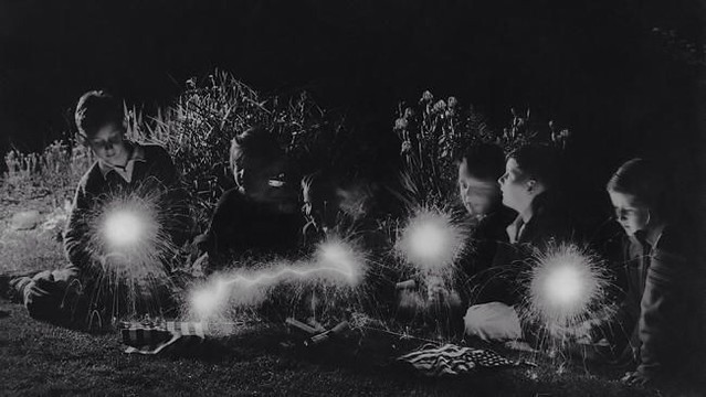 A group of children playing with sparklers after the 4th of July celebrations. 1940