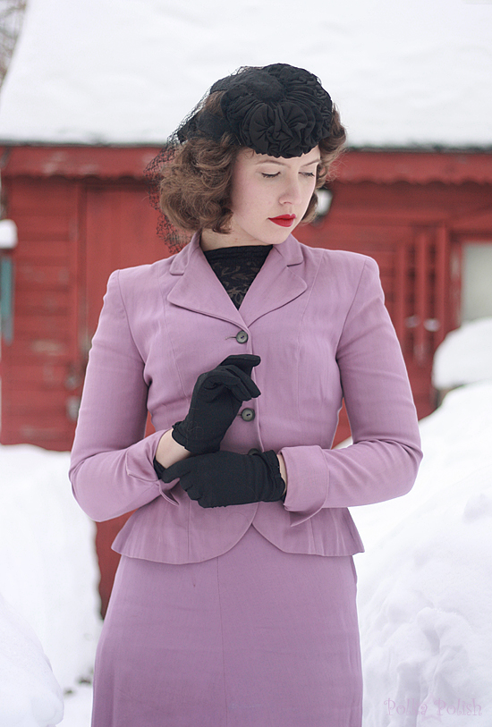 Light purple 1940s suit paired with black gloves and a black tilt hat for winter