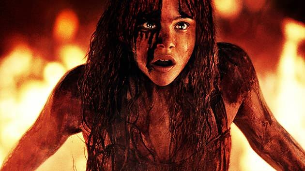 Bloody Chloe Grace Moretz as Carrie White against background of fire