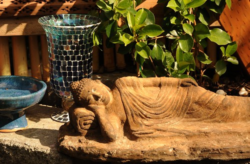 "Statue of Lord Buddha happily reclining on his right side, ushnisha (uṣṇīṣa - topknot - attainment of reliance in the spiritual guide, 1 of 32 ""great marks"" Maha-Laksana), bowl, lantern, leaves, A Garden for the Buddha, Seattle, Washington, USA by Wonderlane"