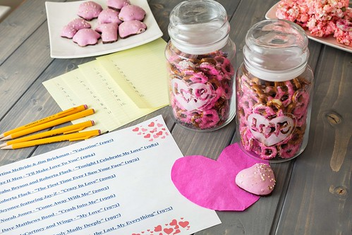 pink Valentine's Day yogurt coated pretzels in a bowl with glass mason jar on wood table with guessing game cards and pencils