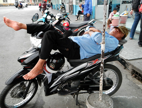 Man Sleeping on his Motorcycle in HCMC