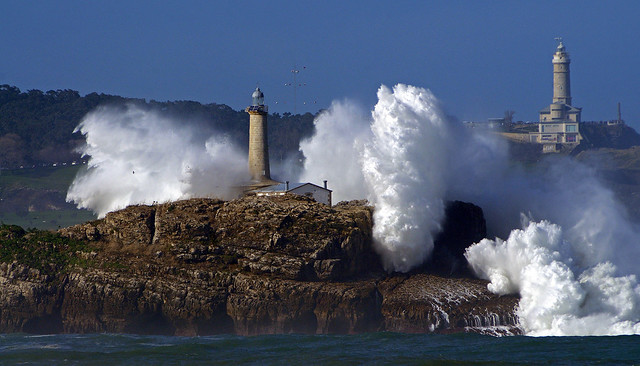 """Faros de Mouro y Cabo Mayor"" photo by Rafael González de Riancho. Powerful swells crash against Faros de Mouro, a lighthouse and islet on the northern coastline of Spain."