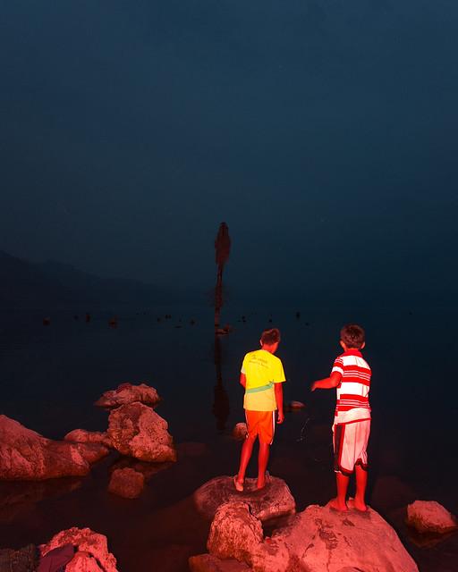 Two kids fishing on the shore of lake Atitlan, San Pedro, Lago Atitlan, Guatemala