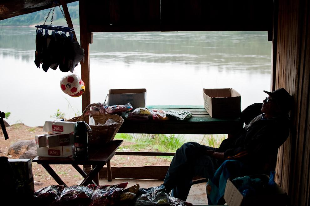 Un anciano espera por clientes en su puesto de venta de artículos varios al pié del Río Paraná. Este señor permanece sentado en su puesto todos los días desde las 8 de la mañana hasta las 19 horas. El pueblo está colmado de pequeños negocios para satisfacer las necesidades de los pasajeros que diariamente cruzan el río. (Elton Núñez)