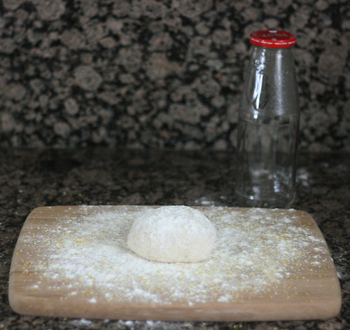 "Pizza dough on prepared surface with ""rolling pin"" equivalent"