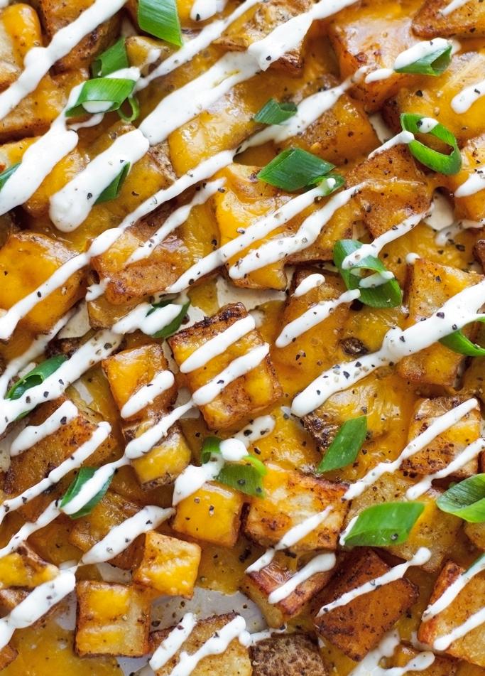 Cheesy Ranch Roasted Potatoes - Baked southwestern potato bites topped with a ranch greek yogurt sauce! #potatobites #potatowedges #vegetarian #greekyogurtsauce #ranchdressing   littlespicejar.com