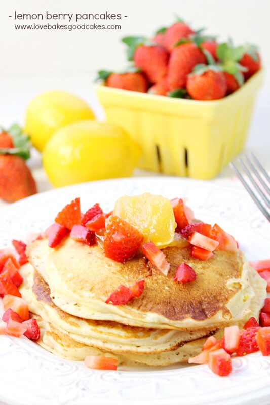 Lemon Berry Pancakes stacked up on a plate with fresh strawberries and a fork.