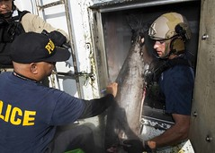 A U.S. Coastguardsman assigned to Pacific Tactical Law Enforcement Team Detachment 108, a Palauan law enforcement official and a Sailor assigned to USS Spruance (DDG 111) inspect a foreign fishing vessel June 3 as part of the Oceania Maritime Security Initiative. (U.S. Navy/MC2 Will Gaskill)