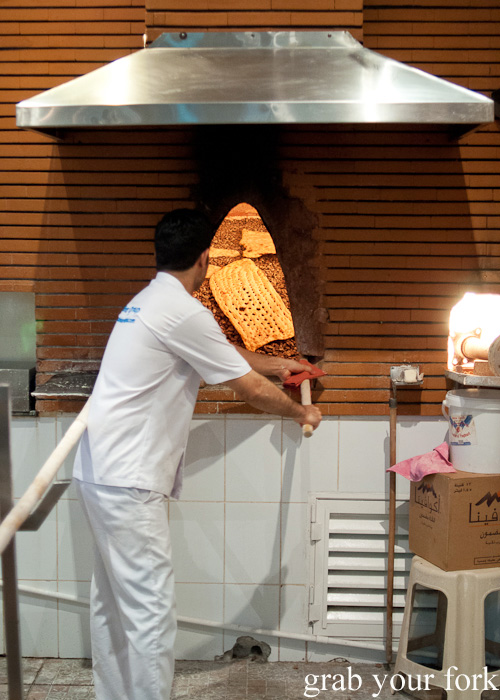 Baking sangak Persian bread on stones during a Frying Pan Adventures food tour in Dubai
