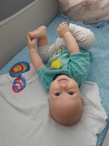 a baby in summer clothes holding onto his own feet. The baby is smiling, his face is upside down to the camera.
