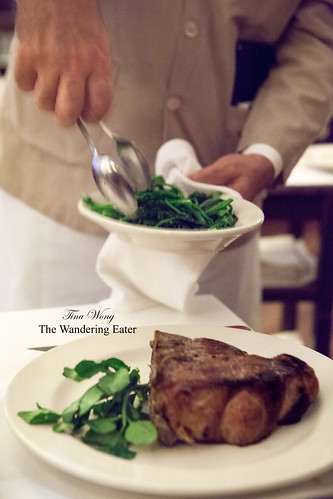 Grilled double-cut veal chop and our waiter serving our broccoli rabe