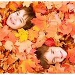 two 6 year old boys laying down in leaves