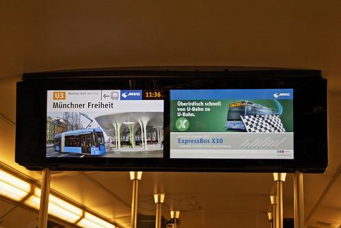 Anzeige an der Münchner Freiheit, rechts die Werbung für den Expressbus X30