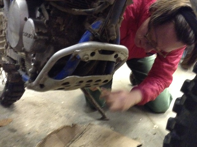 Getting the mud-encrusted skidplate off the DR350 to change the oil