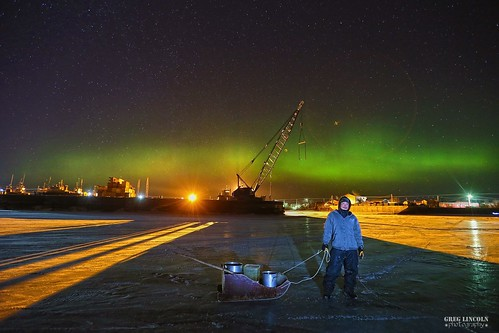 Joe Charlie getting drinking water from the Kuskokwim River as the northern lights dance behind him.
