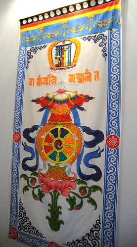 Tibetan door cover: Kalachakra symbol with the 8 Auspicious Symbols of the Buddhist Dharma used as a wall decoration, conch shell umbrella banner of victory fish wheel vase infinity knot flower, stairwell, Lake Otis, Anchorage, Alaska, USA by Wonderlane