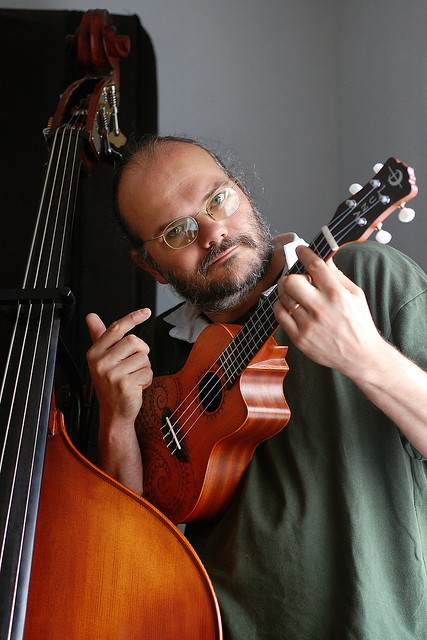 Wulf holding a small ukulele, standing next to his double bass