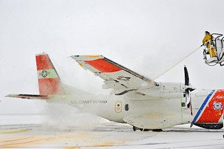 Coast Guard crews prepare for Winter Storm Juno by de-icing an HC-144a Ocean Sentry Aircraft before flying storm tracks to warn mariners about the impending blizzard Jan. 24, 2015. A special mixture of fluids is used to dissolve the ice and prevent ice buildup. (U.S Coast Guard photo by Petty Officer 3rd Class Ross Ruddell)