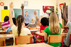 Todd Jesperson: Group of teenagers sitting in classroom with raised hands.