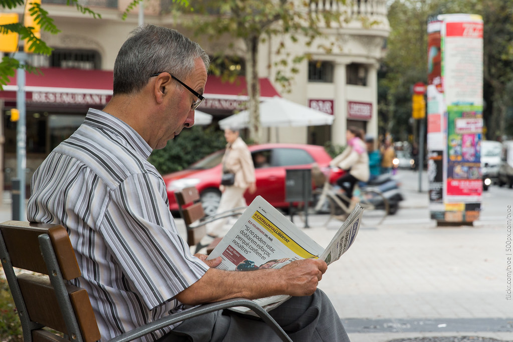 Мужчина читает газету в Барселоне