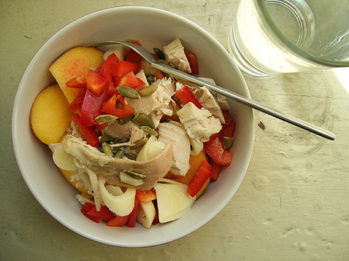chicken, hearts of palm, red pepper, and pepita salad on sliced peaches