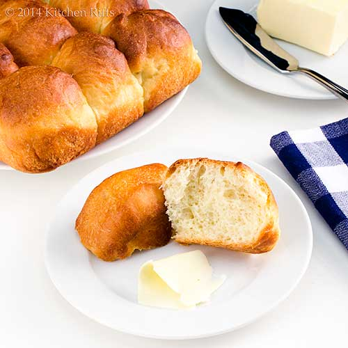 Soft and Buttery Dinner Rolls on plate with butter in background