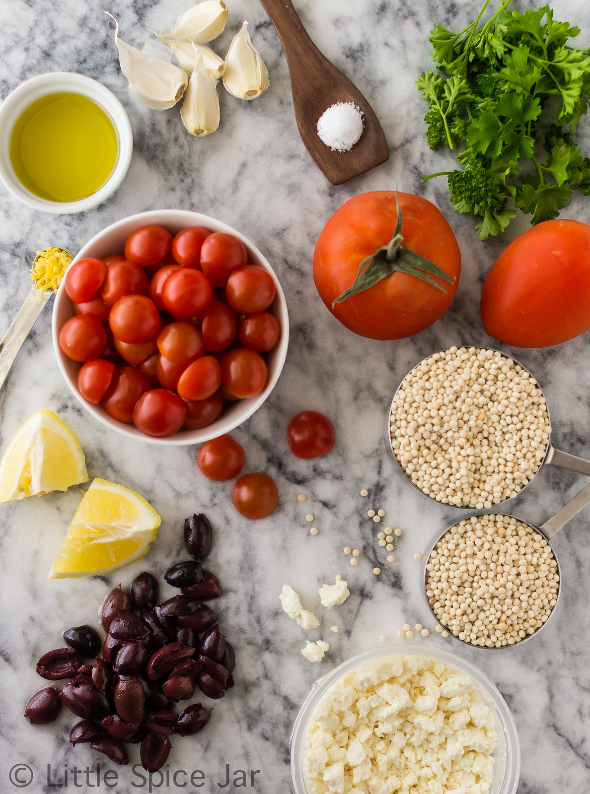 ingredients for mediterranean pearl couscous salad in bowls and scattered on marble
