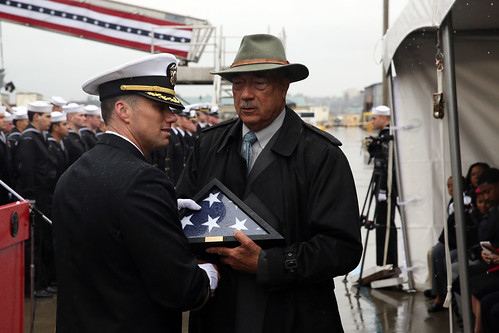 EVERETT, Wash. - Cmdr. Todd E. Whalen, commanding officer of USS Rodney M. Davis (FFG 60), presents the last national ensign flown aboard the ship underway to Gordon Davis, eldest brother of Sgt. Rodney Maxwell Davis, during the ship's decommissioning ceremony.