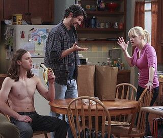 Anna Farris yells at a shirtless man eating a banana