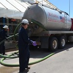 Pueblo Chemical Agent-Destruction Pilot Plant employees attach a tube to a tanker truck to unload the biomass into the Biotreatment Area immobilized cell bioreactors for storage and surrogate testing in preparation for plant operations.