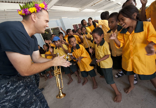 Musician 2nd Class Lee Koelzd dances with children during a Pacific Fleet Band performance