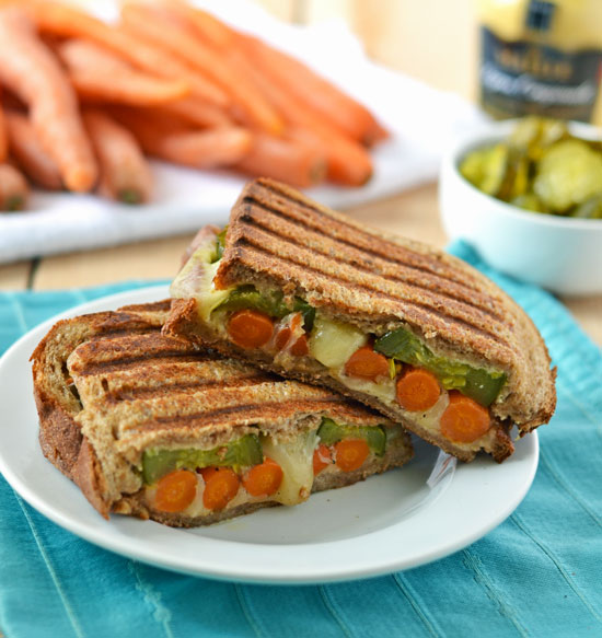Roasted carrot grilled cheese halves on a white plate