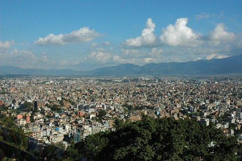 The ancient settlement of Kathmandu as viewed from Swayambhunath Hill, prayer flags, sunny day with a few clouds, trees, ring of mountains, Kathmandu, Nepal by Wonderlane
