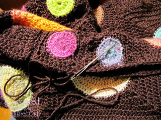 Close-up of a large metal darning needle threaded with dark brown yarn, in the midst of stitching blanket squares together.